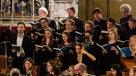 The Armonico Consort's choir are stood in rows singing, the setting is an old church