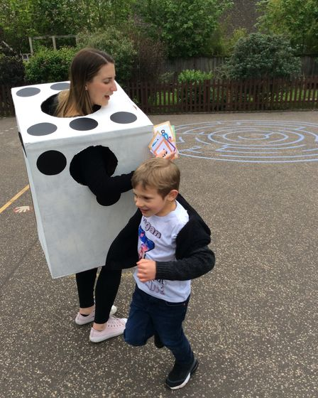 Logan from Year Two taking part in a number hunt, pictured with assistant headteacher Chloe Cole, dressed as a dice, for