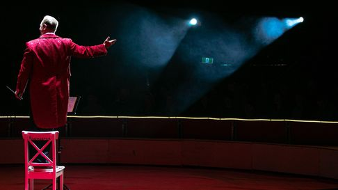 A man in a circus master outfit stands on a chair in the spotlight, arm outstretched