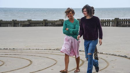 People walking the temporary COVID memorial labyrinth on Overstand beach.
