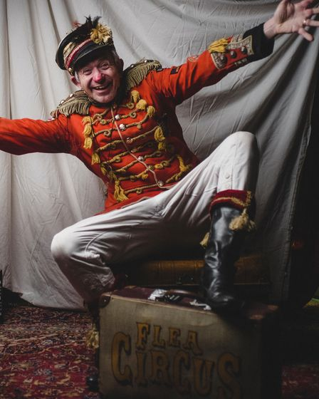 A man in a circus ringmaster outfit, jumping for joy.