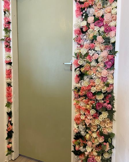 A wall decorated in plastic flowers.