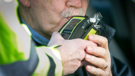 A driver blows into a PSNI Road Policing officers' breathalyser during a random drink driving checkp