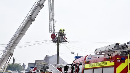 Firefighters use a crane to douse the flames at the bungalow