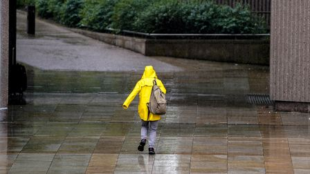 A person runs for cover as the rain falls in Liverpool. Picture date: Friday June 25, 2021.