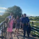 Five people standing on a bridge. They all look very happy. Behind them, there are grassy fields and a clear blue sky.