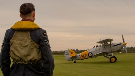 A costumed actor looks on as a Hawker Nimrod II taxies out onto the airfield at IWM Duxford.