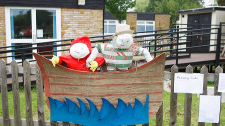 Two scarecrows dressed as sailors are in a paper boat.