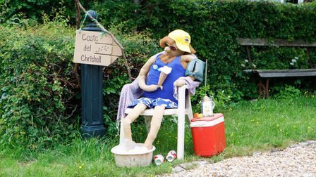 """A scarecrow is on a deckchair, holding an ice cream. A sign: """"Costa del Chrishall"""""""