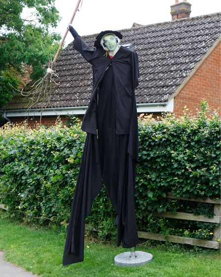 A tall scarecrow dressed as a witch. It holds a wooden broom.