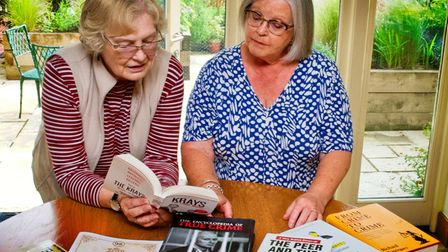 Sue Parry and Susan Riddle look through books about true crime - a