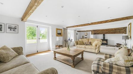 living room with white ceiling and walls, part-glazed white doors, coffee table, beige rug and sofas, wood-burner and beams