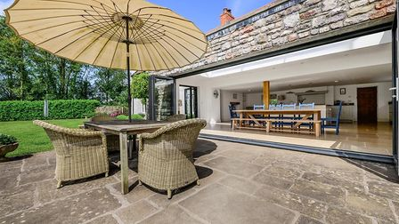 stone patio with table and wicker chairs by the side of a set of large bi-folding doors with the dining room beyond and lawn