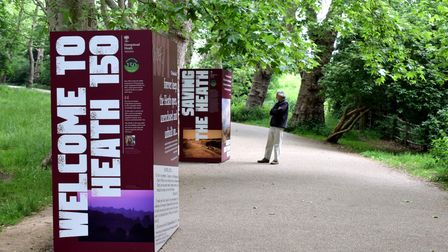 People stop to read the panels on the Heath 150 art installation at the South End Green entrance to Hampstead Heath