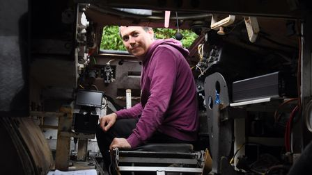 Merlin Batchelor in the driving position of his 1967 armoured personnel carrier, which has led him t