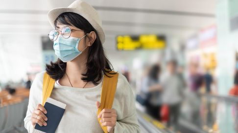 Happy Asian woman wear protective face mask and eyeglasses walking in international airport terminal