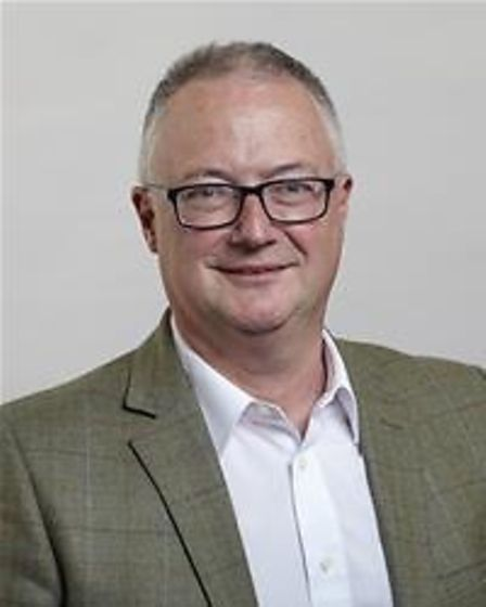 A man wearing a beige blazer and fashionable glasses: Cllr Neil Gregory