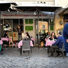 People enjoy a drink at a bar's terrace on Campo dei Fiori in central Rome, on May 18, 2020 as the c