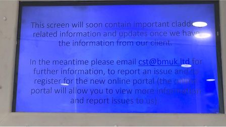 TV screen in St Francis Tower lobby showing a message from BMUK about the cladding