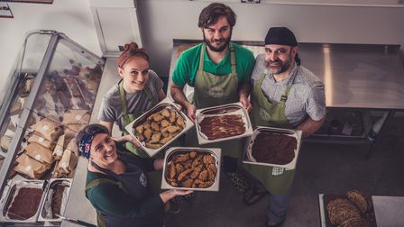 The owners of How On Earth deli in Exeter holding trays of their food.