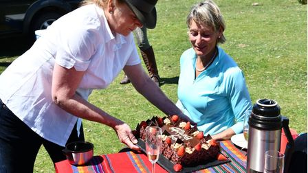 A woman being served a birthday cake whilst sitting outside on a picnic blanket