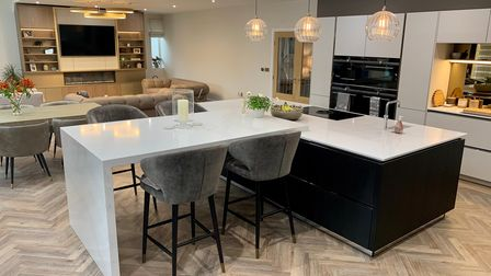 A modern, open-plankitchen with a kitchen island and dining areadesigned by Steven Christopher Design