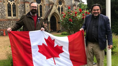 Ian Mackie, community goodwill ambassador and county councillor, with the Revd James Stewart hold the Canadian flag.
