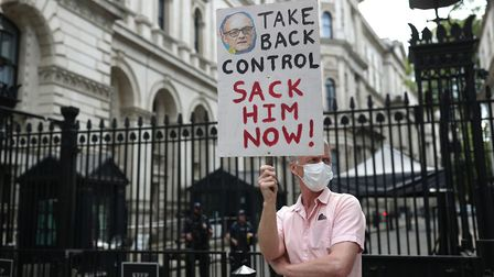 A protester outside Downing Street, London, as the row over Prime Minister Boris Johnson's top aide