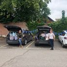 Three cars with their boots open, filled to the brim with bags of clothes and shoes. Also pictured - two volunteers