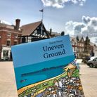 """A blue book with the text: """"Uneven Ground"""". In the background: Saffron Walden Market Square."""