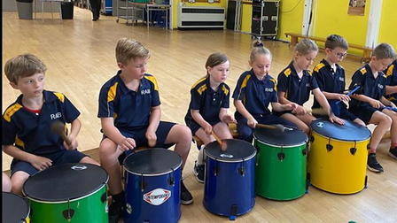 A group of children playing multi-coloured drums at R A Butler Academy, Saffron Walden