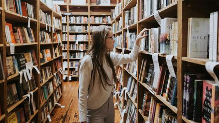 A woman selects a book from a long row of shelves in a bookshop