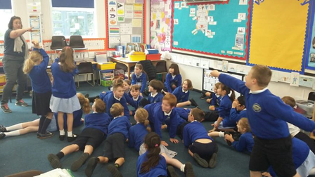 A classroom full of children at R A Butler Academy, Saffron Walden. One of them lunges as if carrying a dagger.