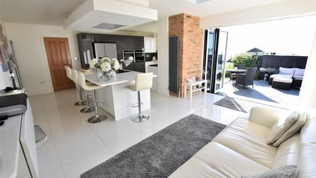 open-plan kitchen-family room with grey gloss units and island with breakfast bar, bi-folding doors and sofa in family area