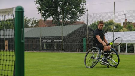 Alfie Hewett hits a topspin backhand to Coach Donna Bailey on the grass courts at Cromer Tennis Club.