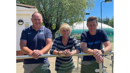 Tennis club officials leaning on net
