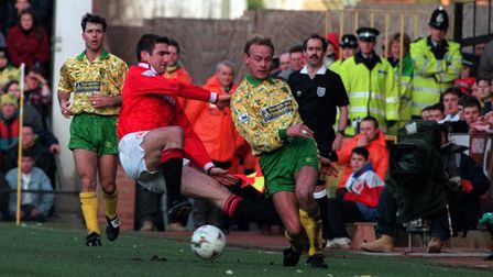 Manchester United's Eric Cantona (foreground Left) charges into Jeremy Goss of Norwich City, during