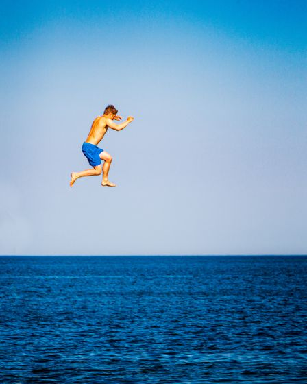 A young boy jumps into the sea