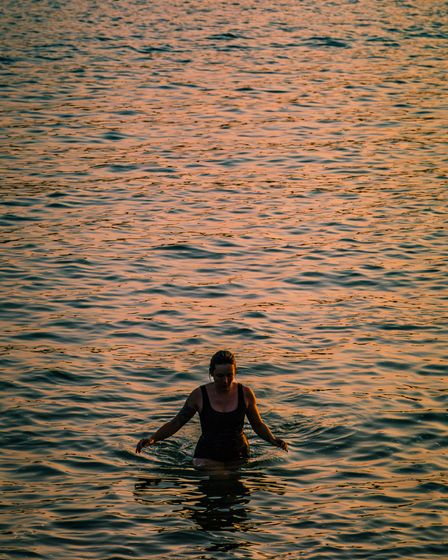 A swimmer enjoys the last light of the day immersed in the water of the Helford River