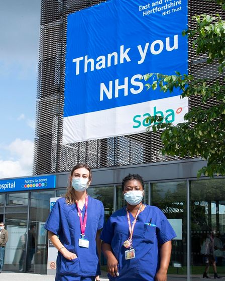 Members of staff pose in front of the thank you NHS banner