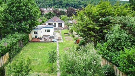 aerial shot of the lawned back garden, cream-rendered garage and bungalow in Knightcott Road, Banwell.