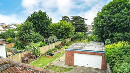 Back of bungalow in Knightcott Road, Banwell, with large detached double garage and lawn to left with raised planters