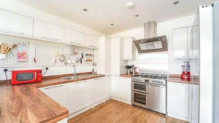 Kitchen with white glossunits, dark wood-effect worktops and floor and stainless-steel range cooker with extractor.