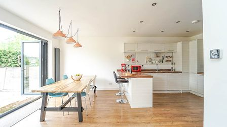 Kitchen with a breakfast bar and stools on right, a table and chairs with downlighters on left, with open bi-folding doors
