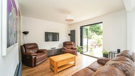 Sitting room with bi-folding doors on right, brown leather sofas with pine coffee table in middle, TV on wall at back