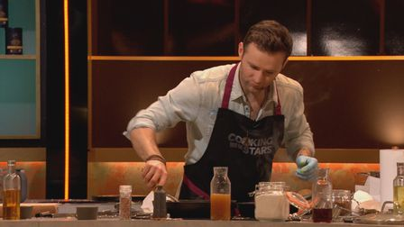 Harry Judd in the kitchen in Cooking With The Stars with a blue glove protecting hisleft hand.