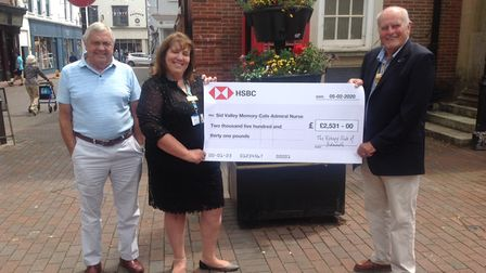 Three people holding a novelty-sized cheque in Sidmouth town centre