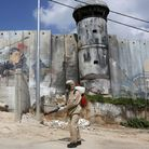 APalestinian sanitary department worker sprays disinfectant alonga security border in Bethlehem, during the pandemic