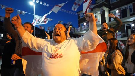 Fans celebrate the goal scored by Harry Kane at Kirby housing estate in Bermondsey while they watch