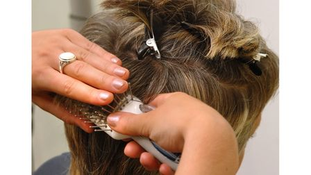 A close-up photo of a hairdresser at work